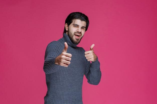 Homem de camisa cinza fazendo sinal de prazer com a mão.