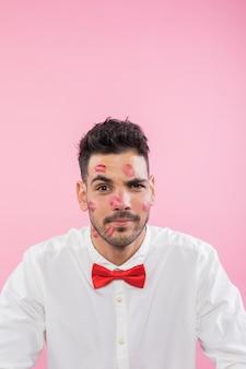 Homem de camisa com marcas de beijo de batom no rosto