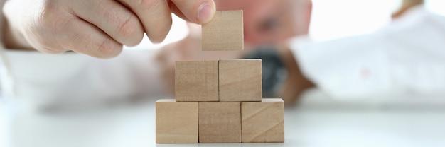 Homem de camisa construir torre de cubos de madeira na mesa do escritório close-up