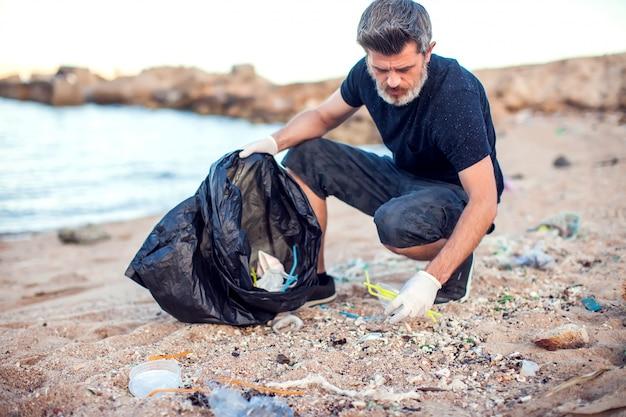 Homem de camisa escura e shorts com luvas brancas e um grande pacote preto coletando lixo na praia. proteção ambiental e conceito de poluição do planeta