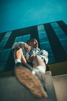 Homem de camisa listrada branca e preta e jeans azul sentado em um banco de concreto marrom