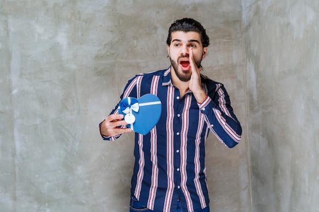 Homem de camisa listrada segurando uma caixa de presente em formato de coração azul e chamando alguém para vir nas proximidades