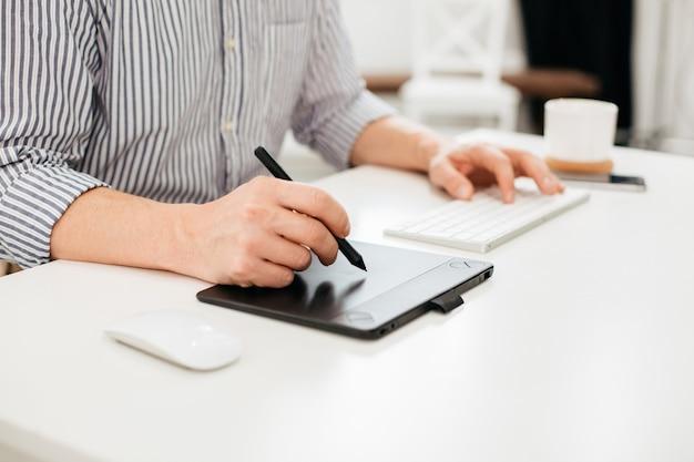 Homem de camisa listrada sentado à mesa e colocando a mão esquerda no teclado e segurando a caneta na mão direita
