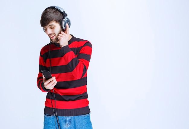 Homem de camisa listrada vermelha, ouvindo fones de ouvido e definindo música de sua lista de reprodução no smartphone.