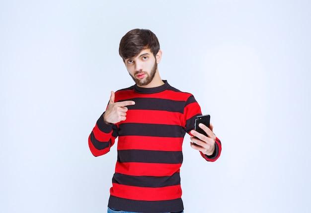 Homem de camisa listrada vermelha segurando um smartphone preto e apontando para ele.