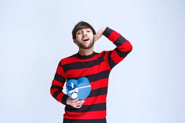 Homem de camisa listrada vermelha, segurando uma caixa de presente da forma de coração azul e ligando ou notando alguém à frente.