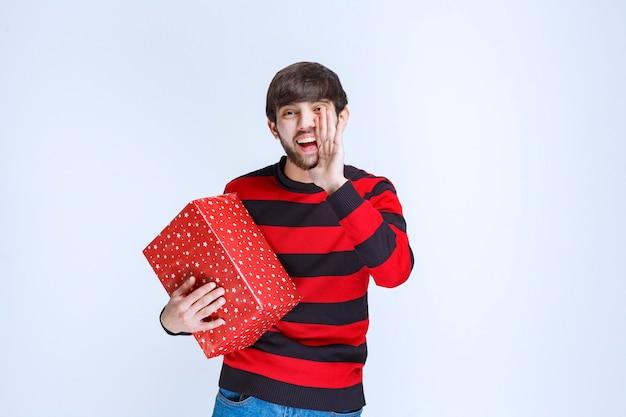 Homem de camisa listrada vermelha, segurando uma caixa de presente vermelha e chamando alguém para entregá-la.