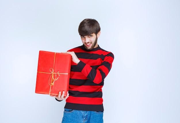 Homem de camisa listrada vermelha segurando uma caixa de presente vermelha, entregando e apresentando-a