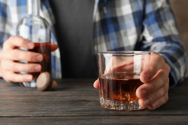 Homem de camisa mantém garrafa e copo de uísque na mesa de madeira, close-up