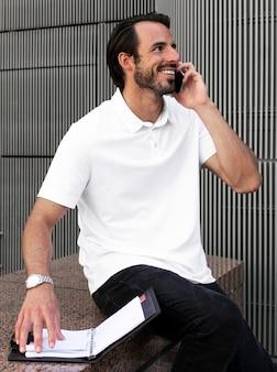 Homem de camisa pólo branca falando ao telefone roupas masculinas, roupas da moda