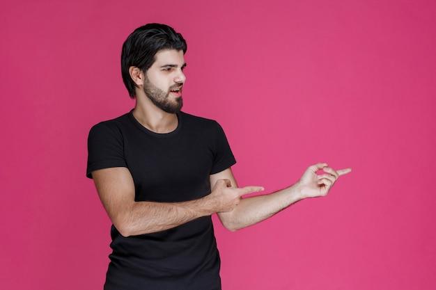 Homem de camisa preta apresentando alguém e apontando para ele