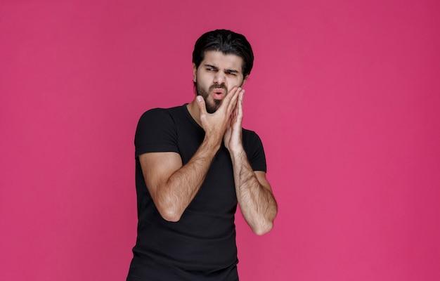 Homem de camisa preta com dor de dente