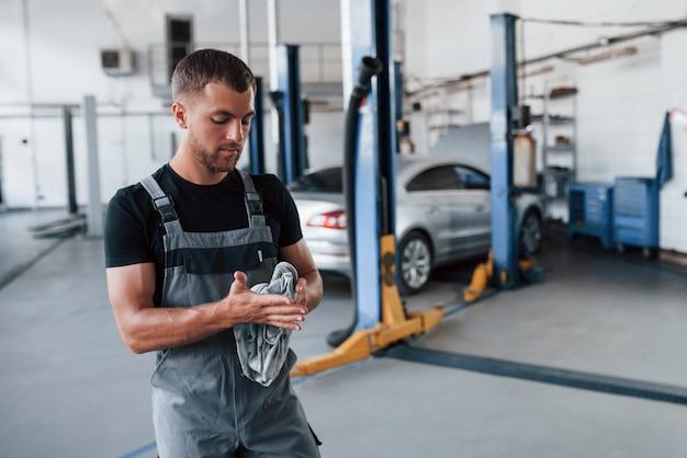 Homem de camisa preta e uniforme cinza na garagem depois de consertar um carro quebrado