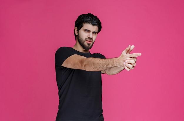 Homem de camisa preta fazendo símbolo de arma de mão