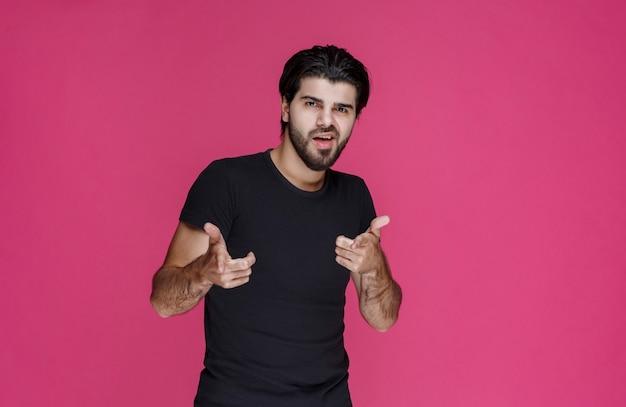 Homem de camisa preta mostra que está gostando completamente de algo