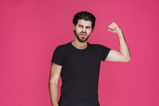 Homem de camisa preta mostrando os músculos do braço