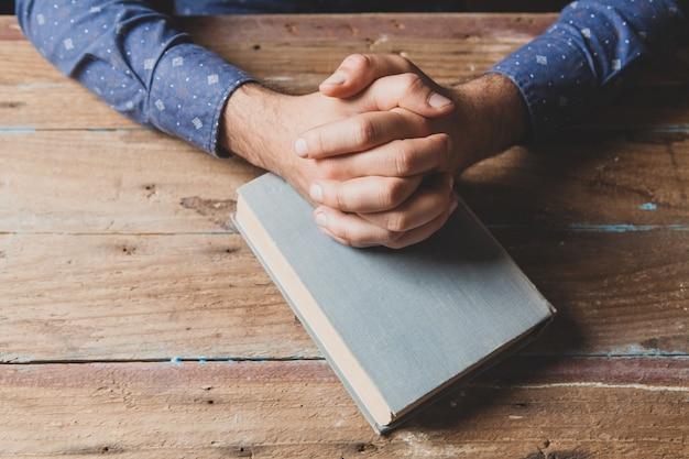 Homem de camisa rezando sobre o livro