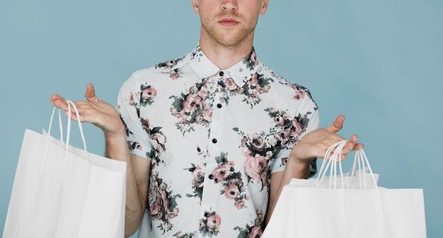 Homem de camisa segurando sacolas de compras em ambas as mãos