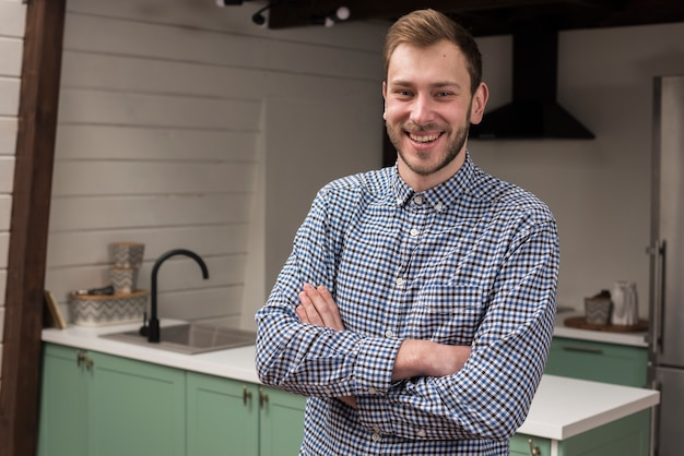 Homem de camisa, sorrindo e posando na cozinha