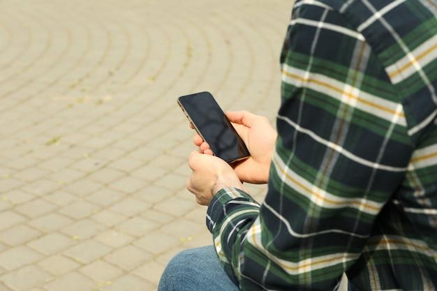 Homem de camisa usando smartphone sentado no parque