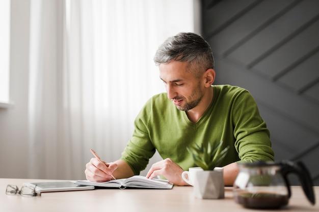 Homem de camisa verde, escrevendo e sentado em sua mesa