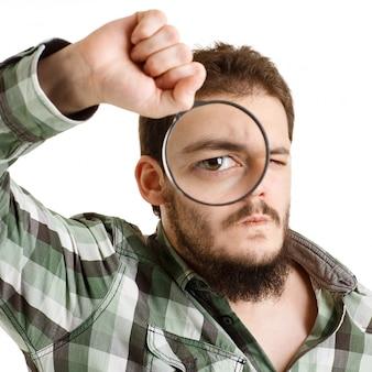 Homem de camisa verde, olhando através de uma lupa.