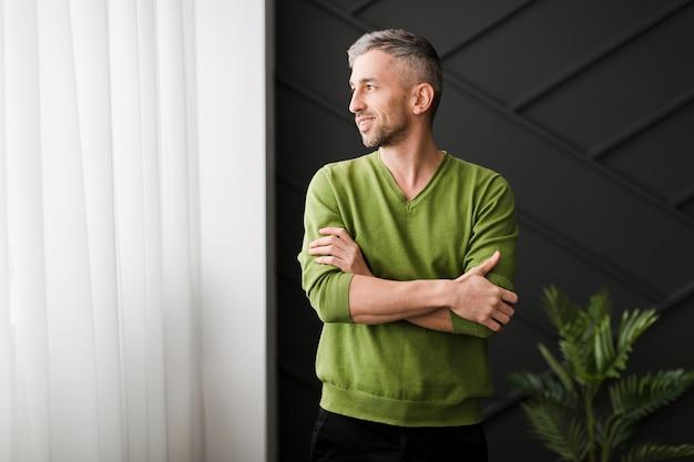 Homem de camisa verde, olhando para a janela