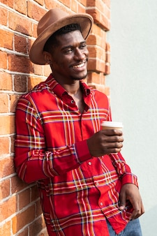 Homem de camisa vermelha encostado na parede e segurando um café