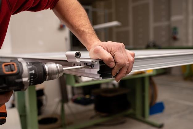 Homem de camisa vermelha fazendo uma janela com ferramentas industriais