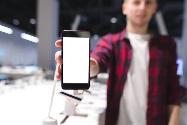 Homem de camisa vermelha mostra um smartphone com uma tela branca
