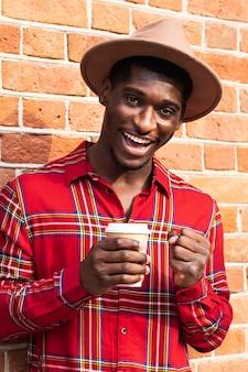 Homem de camisa vermelha sorrindo e segurando café