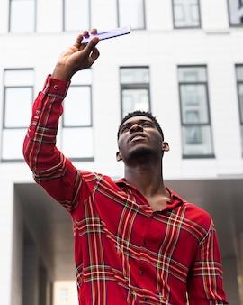 Homem de camisa vermelha tirando uma selfie