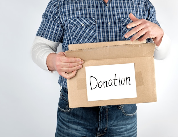 Homem de camisa xadrez azul e jeans detém uma grande caixa de papel marrom com a doação de inscrição