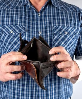 Homem de camisa xadrez azul mantém aberta carteira de couro vazia
