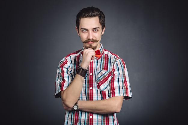 Homem de camisa xadrez e gravata borboleta no estúdio