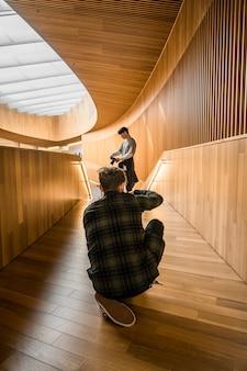 Homem de camisa xadrez preta e branca sentado no chão de madeira marrom tirando uma foto