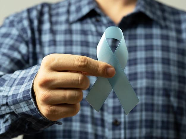 Homem de camisa xadrez tem uma fita azul na mão, um símbolo da conscientização do câncer de próstata.