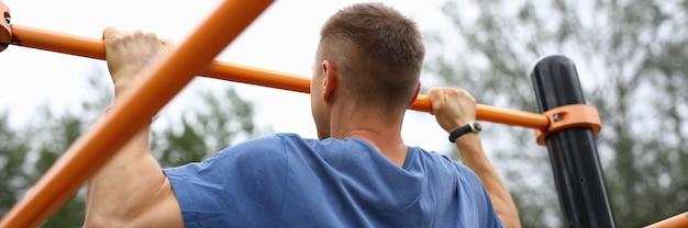 Homem de camiseta azul puxe-se para cima na barra horizontal no parque. atleta inflado faz exercícios em equipamentos esportivos.