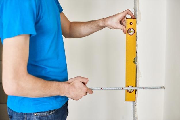 Homem de camiseta azul verifica o nível da parede. o capataz verifica o trabalho realizado