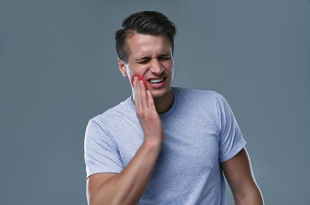 Homem de camiseta branca com dor de dente na sala cinza