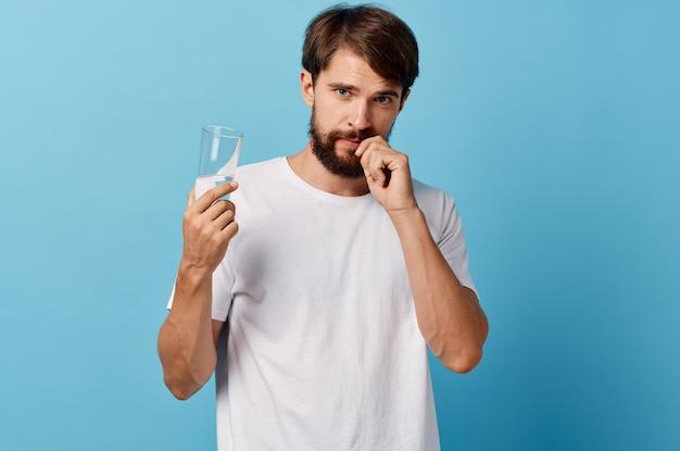 Homem de camiseta branca, copo de água com fundo azul