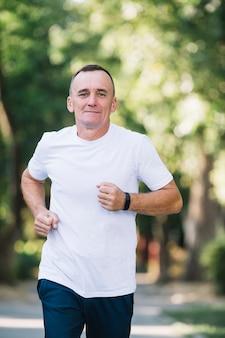 Homem de camiseta branca correndo em um parque