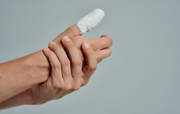 Homem de camiseta branca dedo quebrado enfaixado remédio