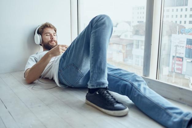 Homem de camiseta branca deitado no parapeito da janela com fones de ouvido divertidos