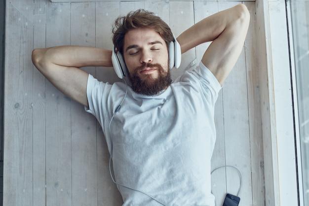 Homem de camiseta branca deitado no parapeito da janela usando fones de ouvido hipster