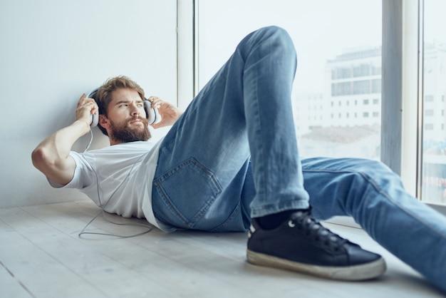 Homem de camiseta branca deitado no parapeito da janela usando tecnologia de fones de ouvido