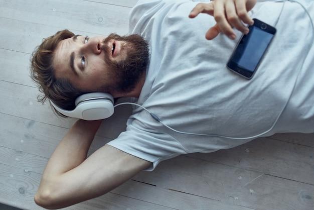 Homem de camiseta branca deitado perto da janela usando tecnologia de fones de ouvido