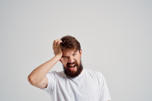 Homem de camiseta branca, dor de cabeça, enxaqueca, fundo claro