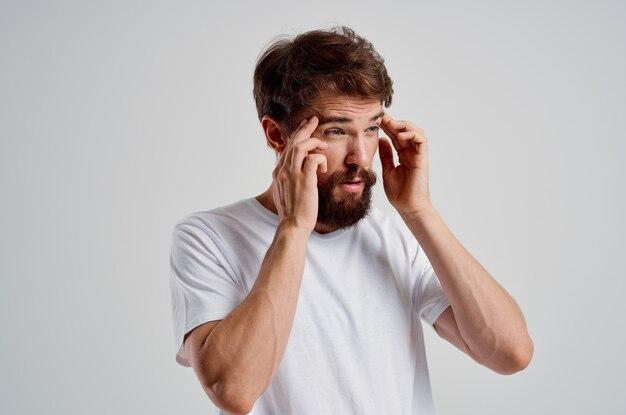 Homem de camiseta branca, dor de cabeça, enxaqueca, fundo isolado