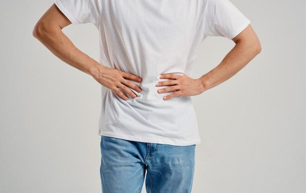 Homem de camiseta branca e jeans tocando a barriga com as mãos dor de estômago indigestão
